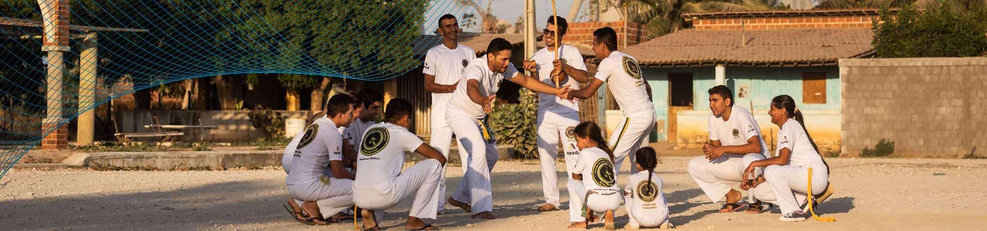 crianças, jovens e adultos praticam capoeira em uma roda